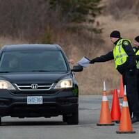 Deux agents près d'une voiture semblent vérifier des papiers appartenant au conducteur.