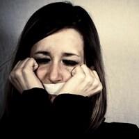 Une femme en pleurs avec un ruban adhésif lui couvrant la bouche.