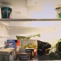 Un réfrigérateur dont les tablettes sont partiellement remplies.