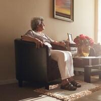 Une femme dans la soixantaine assise dans un fauteuil dans le salon d'une maison.