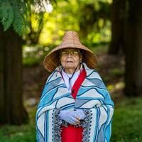Une dame âgée porte un chapeau de paille traditionnelle autochtone et une couverture tradiotnnelle blanche et bleue. Elle est debout dans la forêt.