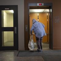 Une femme de dos avec un sac entre dans un ascenseur.