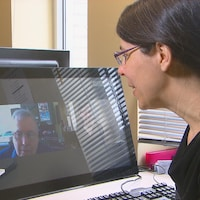 Une femme a une conversation par ordinateur avec un aîné.