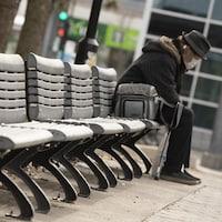 Un homme âgé avec un masque assis sur un banc public.