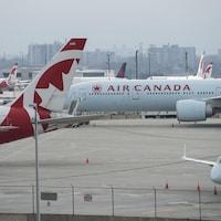 Des avions d'Air Canada attendent sur le tarmac de l'aéroport Pearson, à Toronto.