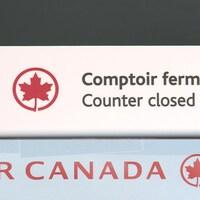 Un comptoir de service fermé d'Air Canada dans un aéroport.
