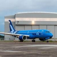 Un A220 d'Airbus peint en bleu et sur lequel on peut lire « Breeze ».