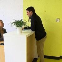 Une homme parle à une femme assise derrière un bureau à l'entrée de la clinique.