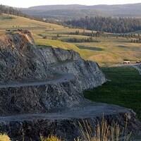 Image d'un champ avec une mine à ciel ouvert à l'avant-plan.