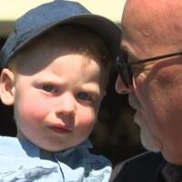 Homme chauve à lunettes regarde petit garçon à casquette.