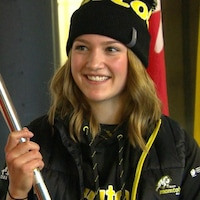 Alana Lesperance souriante et habillée en vêtements d'hiver portant un drapeau à la main.