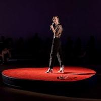 Un homme se trouve sur une scène rouge avec un micro à la main.