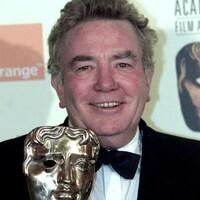 L'homme sourit et tient un trophée en forme de visage.
