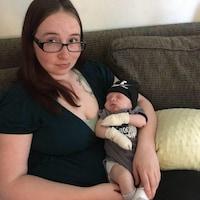 Dans l'image, le nouveau-né dans les bras de sa mère assise sur un sofa.