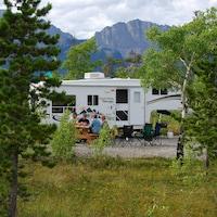 Quatre campeurs sont installés à une table de pique-nique, devant une caravane installée dans un terrain de camping de montagne.