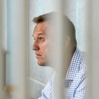Un homme portant une chemise à carreaux est photographié derrière ce qui semble être des barreaux.