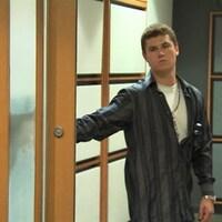 Un homme ouvre une porte dans un corridor.