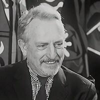 Plan rapproché du peintre Alfred Pellan, devant des costumes qu'il a conçus.