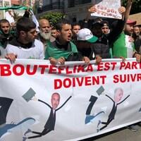 Des manifestants tiennent une banderole dans les rues d'Alger.