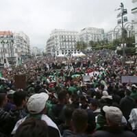 Des manifestants brandissent des drapeaux et des banderoles lors de manifestations pacifiques contre le gouvernement à Alger.