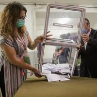 Une boîte de scrutin transparente est vidée de son contenu en vue du dépouillement,
