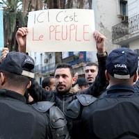 Les manifestants sont bloqués par un cordon de policiers. Un homme tient une pancarte où on peut lire « Ici, c'est le peuple ».