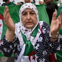 Une femme voilée et portant un drapeau algérien dans le cou applaudit au milieu d'une manifestation.