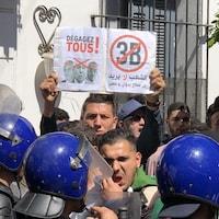 Un jeune tient une pancarte sur laquelle on peut voir les « 3B » marqués d'un X rouge. Devant lui, des policiers anti-émeute.