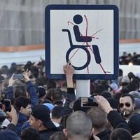 Un gros X rouge barre l'homme en chaise roulante sur la pancarte.