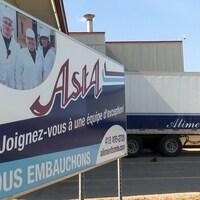 Une affiche et un camion avec le logo d'Aliments Asta sont près d'un bâtiment.