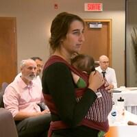 Elle assiste à une réunion avec son bébé dans les bras.