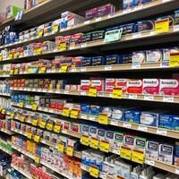 Une allée dans une pharmacie avec plusieurs boîtes contenant des médicament, comme benadryl, tylenol et advil.