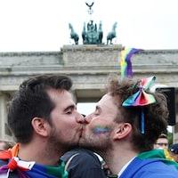 Deux hommes s'embrassant devant la porte de Brandebourg, en juin dernier, lorsque le parlement allemand a adopté la loi autorisant les mariages homosexuels