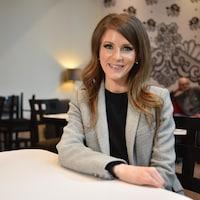 Amanda Simard, assise à une table dans un café, sourit à la caméra.