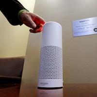 Une main allume l'assistant personnel intelligent Echo, un appareil fabriqué par Amazon