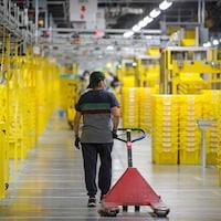 Un employé portant un masque de protection tire un chariot dans un entrepôt.