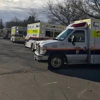 Au moins 5 ambulances dans une rue.