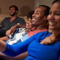 Un groupe d'amis qui s'amusent en regardant la télévision.