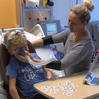 Un enfant est dans un lit d'hôpital, sa mère tient un respirateur sur sa bouche.