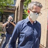 André Boisclair porte des lunettes et un masque et est entouré de photographes.