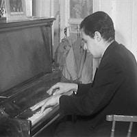 André Mathieu, dos courbé et yeux fermés, qui joue sur un petit piano.
