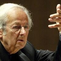 Le chef d'orchestre dirige des musiciens, la main levée.