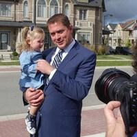 Le chef conservateur tient une enfant dans ses bras.