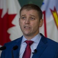 Andrew Furey devant un drapeau du Canada et un drapeau de Terre-Neuve-et-Labrador.