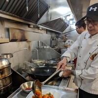 Andrew Mok travaille devant les fourneaux au côté d'un autre cuisinier