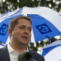 Andrew Scheer tient un point de presse sous la pluie. Derrière lui, se trouve une rangée de parapluies aux couleurs conservatrices.