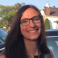 Anne Chamandy, photographiée à l'extérieur, sourit.