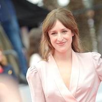 La comédienne porte une robe d'un rose pâle satiné et sourit.
