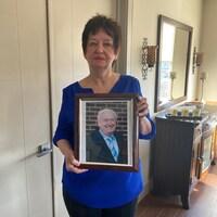 Anne MacPhee porte la photographie de son défunt époux.