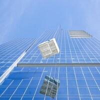 Une unité de ventilation tirée par un monte-charge devant un gratte-ciel.